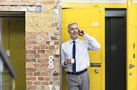 Businessman leaning in front of elevator using smartphone, drinking coffee - FKF02605