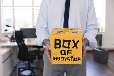 Businessman collecting innovative suggestions in yellow box - FKF02614