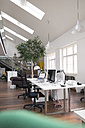 Desks with PCs in bright and modern open space office - FKF02620