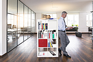 Businessman leaning against shelf, using digital tablet - FKF02647