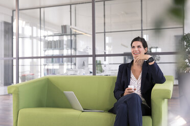 Businesswoman with laptop sitting on a couch and drinking coffee in the office - FKF02701