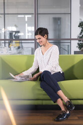 Businesswoman sitting on a couch in the office, looking at documents - FKF02704