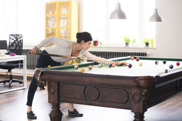 Determined businesswoman playing pool billard in modern office - FKF02713