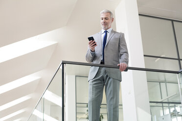 Businessman standing in office using his mobile phone - FKF02719