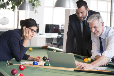 Business people standing at pool table with laptop, discussing investment strategy - FKF02728