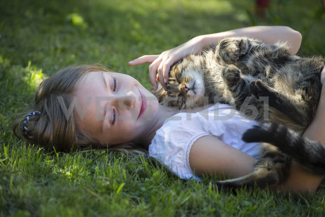 Girl lying with cat in garden - SARF03392