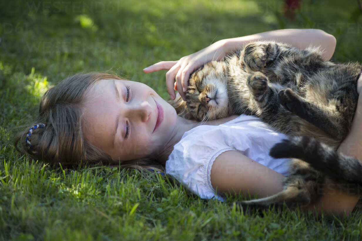 Girl lying with cat in garden - SARF03392 - Sandra Roesch/Westend61