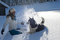 Austria, Altenmarkt-Zauchensee, happy young woman playing with dog in snow - HHF05519