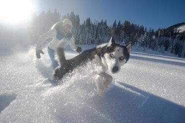 Austria, Altenmarkt-Zauchensee, happy young woman running with dog in snow - HHF05522