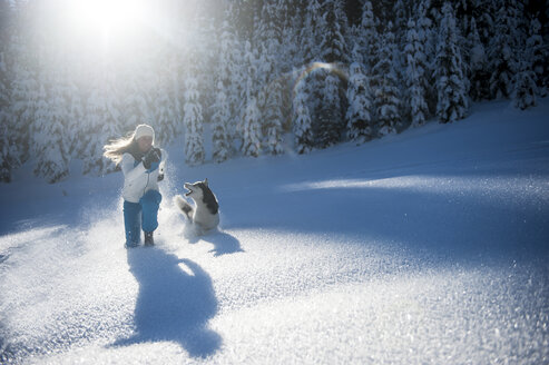 Austria, Altenmarkt-Zauchensee, happy young woman running with dog in snow - HHF05525