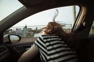 Young woman leaning out of car window - FEXF00311