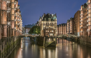 Germany, Hamburg, Speicherstadt, lighted old buildings with Elbe Philharmonic Hall in the background - PVCF01099