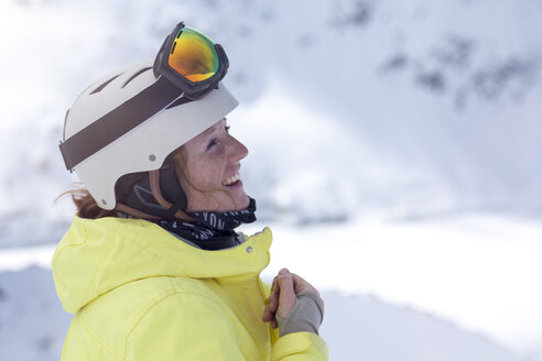 Austria, Kuehtai, happy woman with ski helmet in the mountains - MMAF00165