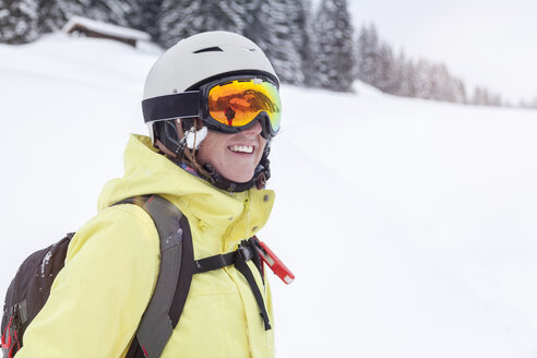 Austria, Kitzbuehel, smiling woman with ski helmet and avalanche backpack in the mountains - MMAF00168