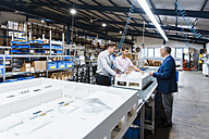 Business people standing on shop floor, discussing product improvement - DIGF02966