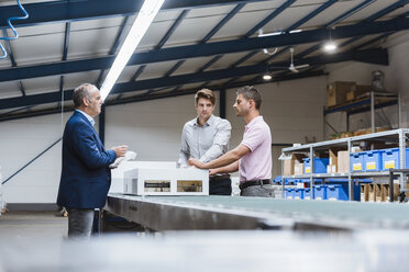Business people standing on shop floor, discussing product improvement - DIGF02969