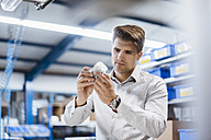 Businessman standing in shop floor, testing products - DIGF02972