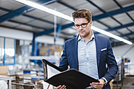 Portrait of a young manager in the shop floor, holding file - DIGF02984