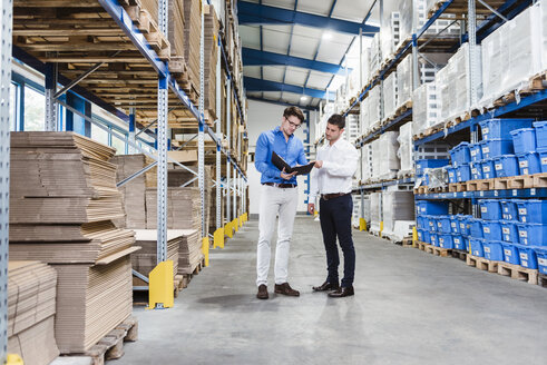 Two businessmen having a meeting in company warehouse - DIGF02995