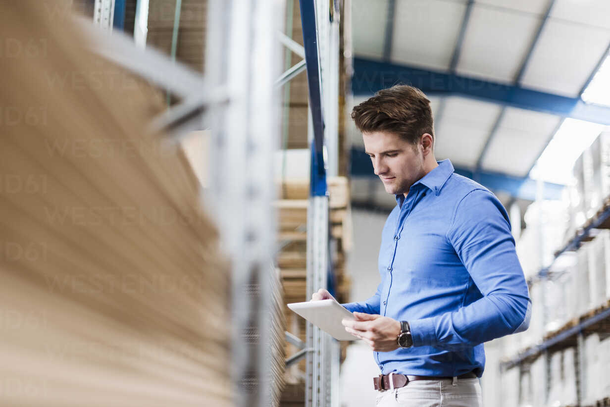 Young man working in warehouse, using digital tablet - DIGF03001 - Daniel Ingold/Westend61