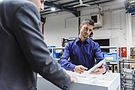 Business people standing on shop floor, discussing product improvement - DIGF03034