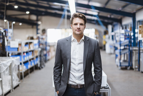 Young manager standing in shop floor, portrait - DIGF03037