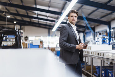 Young manager standing in shop floor with digital tablet, portrait - DIGF03040