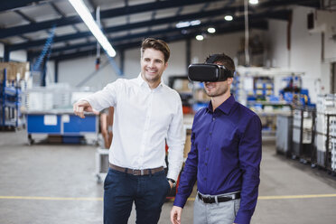 Two employees having a meeting, one wearing VR goggles - DIGF03043
