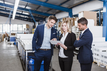 Three business people discussing on shop floor, using digital tablet - DIGF03058