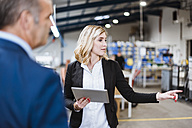 Businesswoman talking to business founder, holding digital tablet - DIGF03064