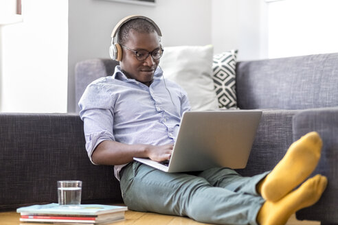 Young man sitting on the floor in the living room using laptop and headphones - MMAF00180