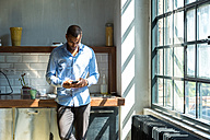 Young entrepreneur standing in company kitchen, drinking coffee, using smartphone - SPCF00208