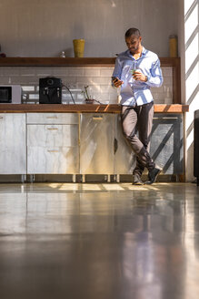 Young entrepreneur standing in company kitchen, drinking coffee, using smartphone - SPCF00211
