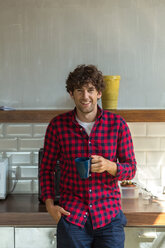 Young entrepreneur standing in company kitchen, drinking coffee - SPCF00220
