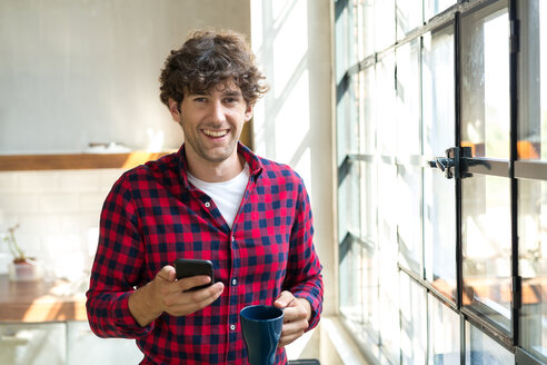 Young entrepreneur standing in company kitchen, drinking coffee, using smartphone - SPCF00223