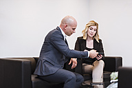 Businessman and businesswoman sitting on couch sharing tablet - DIGF03076