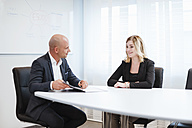 Businessman and businesswoman talking in office - DIGF03085
