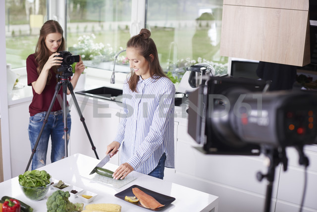 Woman recording her friend while chopping a courgette - ABIF00023