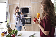 Woman recording friend while preparing healthy food - ABIF00026