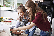Bloggers using laptop and camera in kitchen - ABIF00032