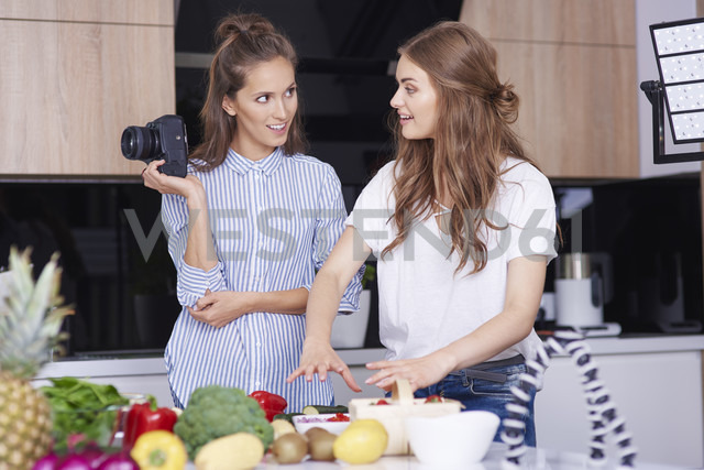 Food bloggers with camera talking in kitchen - ABIF00041
