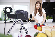 Woman recording while chopping vegetables - ABIF00047