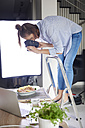 Woman standing on step ladder and photographing food - ABIF00062