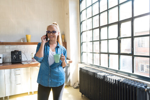 Portrait of smiling businesswoman on the phone standing with coffee mug in the kitchen - SPCF00250
