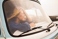 Spain, Tenerife, laughing young woman sitting in van behind windscreen - SIPF01827