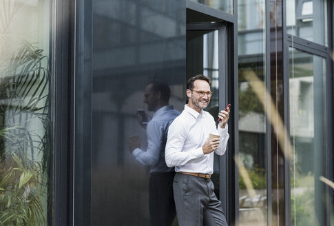 Businessman with coffee to go using cell phone in front of office building - UUF12071