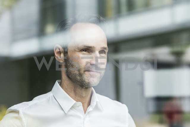Portrait of smiling businessman looking out of window - UUF12077