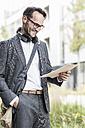 Smiling businessman reading documents - UUF12083