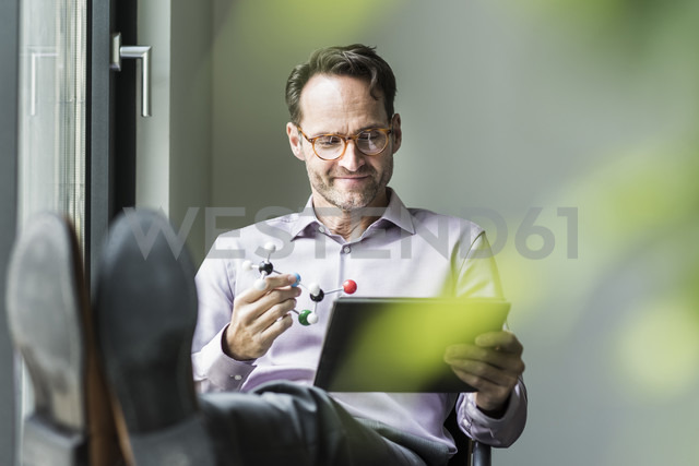 Portrait of smiling man with atomic model and tablet - UUF12086