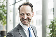 Portrait of smiling businessman with stubble - UUF12092